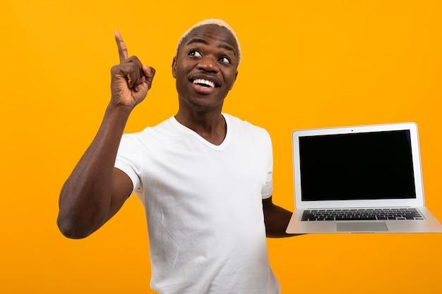 Американский мужчина с белыми волосами, улыбаясь, держа экран ноутбука вперед с макет, подняв палец на желтом фоне