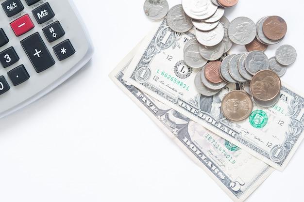 コピースペースと白い背景に電卓とアメリカのお金のドル