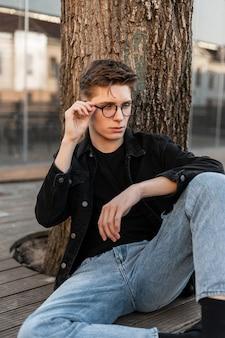 빈티지 데님 옷을 입은 미국의 멋진 트렌디 한 젊은이 모델이 안경을 곧게 만듭니다.