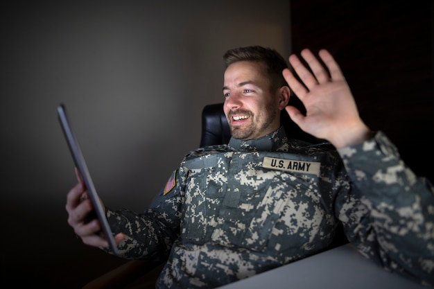 American off duty soldier in military uniform holding tablet computer waving to his family