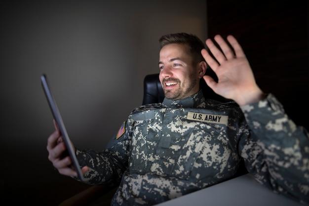 Soldato fuori servizio americano in uniforme militare che tiene computer tablet salutando la sua famiglia