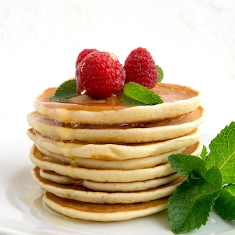 American pancakes with berries on a light background.