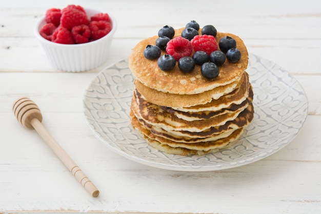 American pancakes with raspberries and blueberries on white wooden table