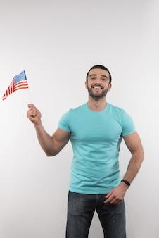 Американский патриот. довольный милый мужчина держит флаг сша, глядя на вас