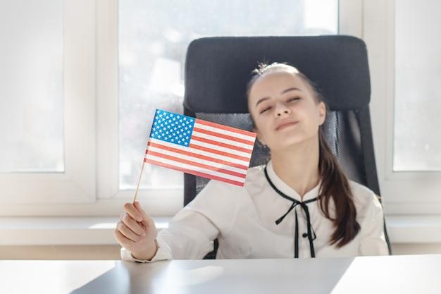 アメリカの国旗を振るアメリカの愛国者の女の子