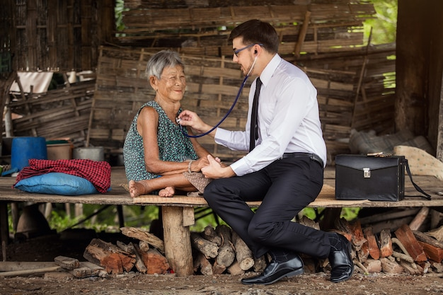 American physician examines elderly asian patients using a hearing aid.