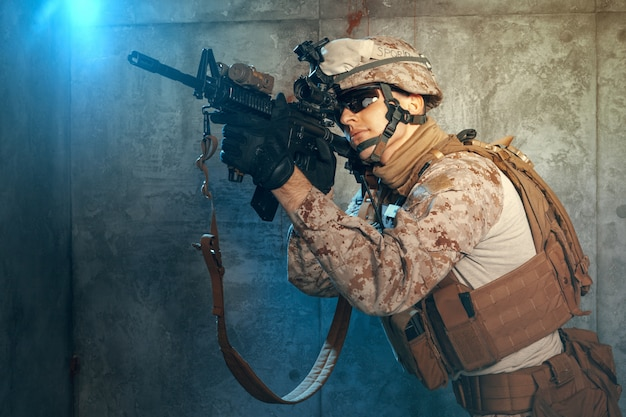 American private military contractor shooting a rifle. studio shot