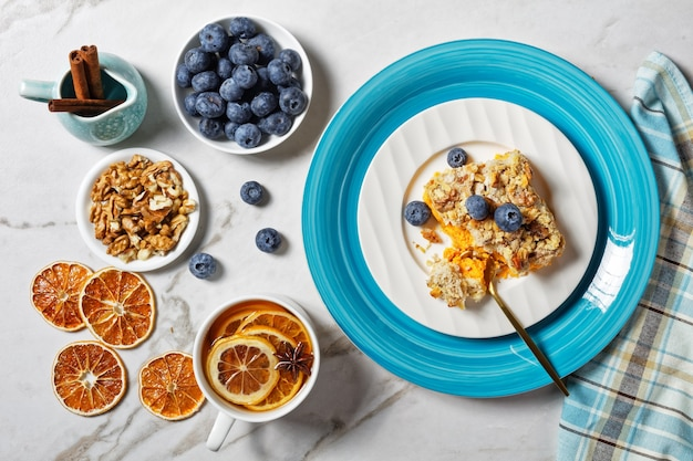 American pumpkin dump cake: fast and easy fall dessert with cinnamon, clove, nutmeg with walnuts and oats on top served on a plate with blueberries on white marble background, top view, close-up