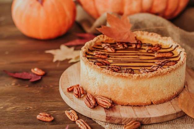 American pumpkin pie decorated with chocolate and pecan nuts on a wooden table