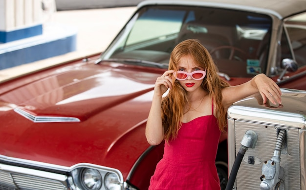 Американский ретро-автомобиль. заправочная станция, женщина заправляет машину. красный ретро-автомобиль.