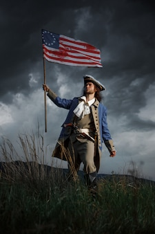 American revolution war soldier with flag of colonies over dramatic landscape