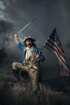 American revolution war soldier with flag of colonies and saber over dramatic landscape