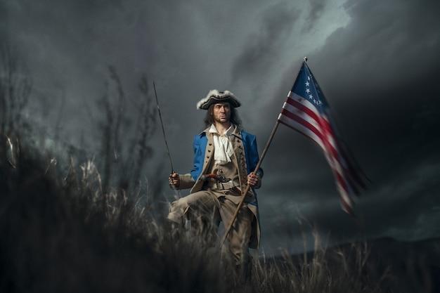 植民地の旗と劇的な風景のサーベルを持つアメリカ革命戦争の兵士