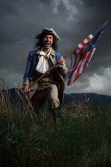 劇的な景観上の植民地の旗を持つアメリカ革命戦争兵士