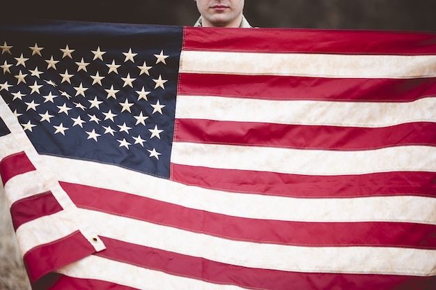 Американский солдат держит американский флаг
