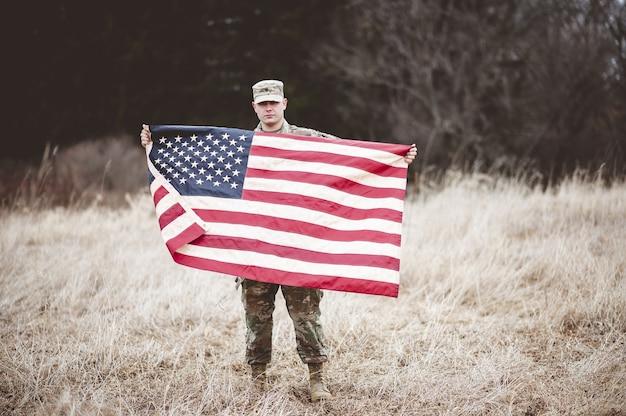 アメリカの国旗を持っているアメリカの兵士