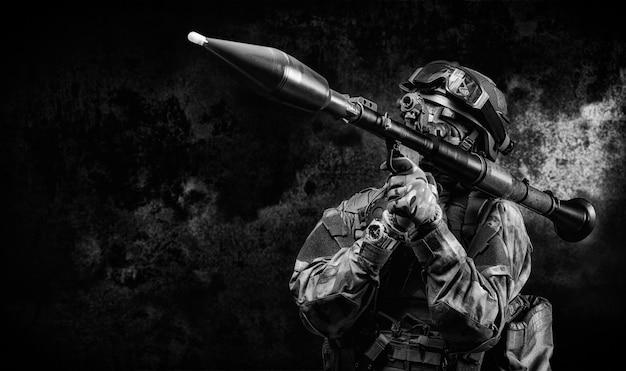 アメリカの兵士は暗い背景に対してrpgの照準器を目指しています。軍事特殊作戦の概念。ミクストメディア