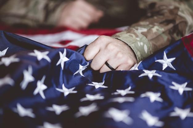 Американский солдат скорбит и молится с американским флагом перед ним