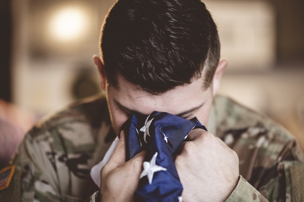 American soldier mourning and praying with the american flag in his hands