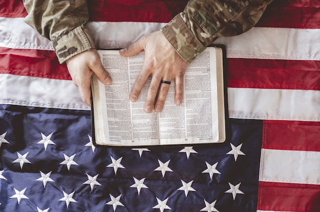 American soldier mourning and praying with the bible in his hands and the american flag