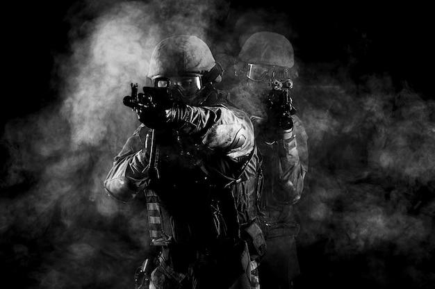 Американские солдаты в боевой амуниции с оружием в руках, оснащенными лазерными прицелами, в боевом порядке. смешанная техника
