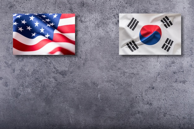 American and soutth korea flags. usa and south korea flag on concrete background.