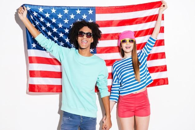 アメリカンスタイル。アメリカの国旗に立ちながら笑顔でカメラを見ているファンキーな若いカップル