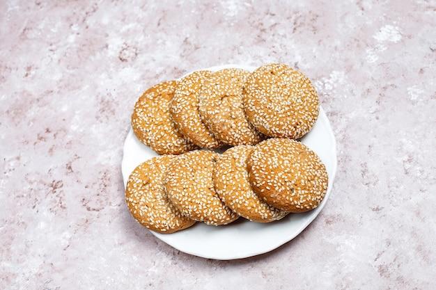 Печенья семени сезама американского стиля на светлой конкретной предпосылке.
