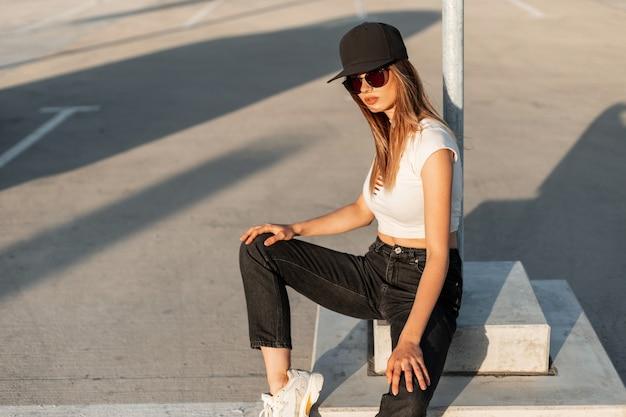 トレンディなジーンズとスニーカーのセクシーな白いトップのファッションブラックキャップのアメリカのスタイリッシュな女の子のヒップスターは、夏の晴れた日に屋外のアスファルトで休みます。路上でカジュアルな若者の服を着た若い都会の女性。