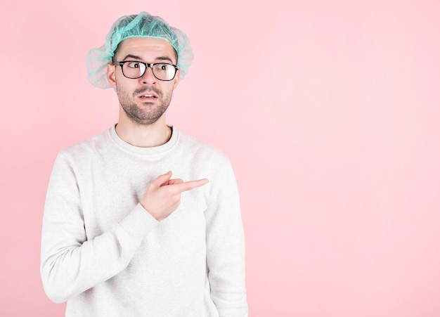 American surgeon doctor man on a pink wall looks surprised and pointing to the side.