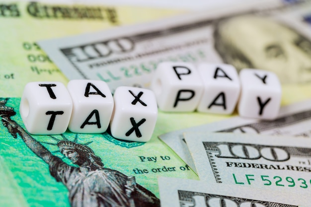 American tax 1040 form and refund check and usa currency hundred dollar bills pay tax
