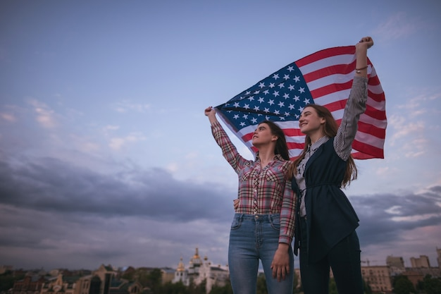 American teens with flag travel around the world. happy girls on roof. teenager sisters on vacation celebrate the independence day on sky background