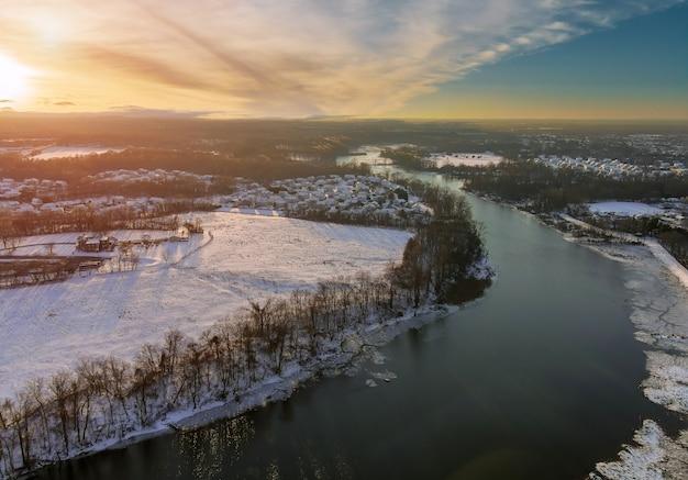 降雪後のアメリカの町アメリカの郊外の都市の冬の昼間の空中写真と川のそばの住宅街で覆われた雪