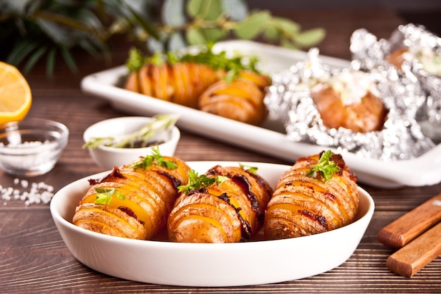 American traditional homemade hasselback potato and stuffed potatoes with fresh herbs and bacon.