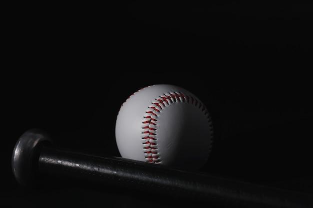 Американская традиционная спортивная игра. бейсбол. концепция. бейсбольный мяч и биты на черном столе.
