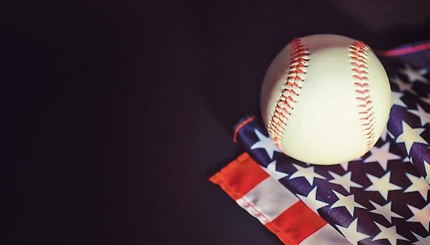 Американская традиционная спортивная игра. бейсбол. концепция. бейсбольный мяч и биты на столе с американским флагом.