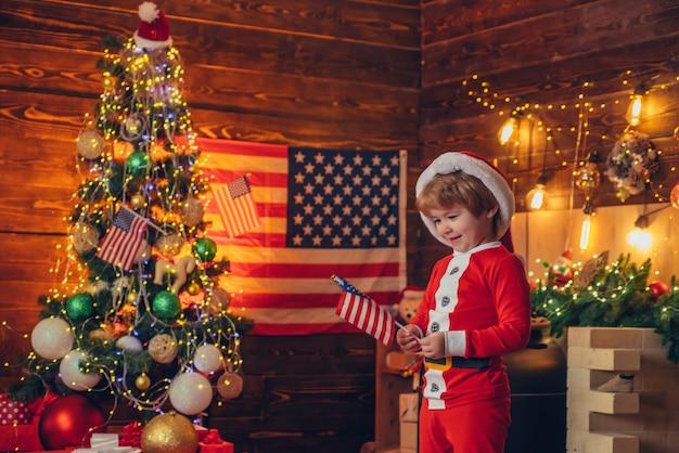 미국의 전통 개념. 귀여운 아기 유아는 크리스마스를 축하합니다. 미국 아이 쾌활한 분위기 흔들며 깃발. 아이 놀이 미국 국기 크리스마스 트리. 작은 소년 산타 모자와 의상 재미.