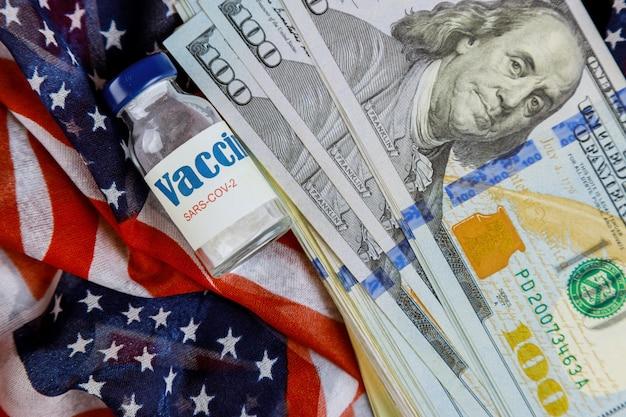 백그라운드에서 미국 미국 달러 지폐 미국 국기와 함께 미국 백신 코로나 바이러스 covid-19 sars-cov-2
