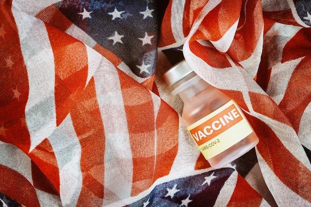 Американская вакцина из стеклянных контейнеров с коронавирусом sars-cov-2 covid-19 для борьбы с пандемией коронавируса с флагом сша
