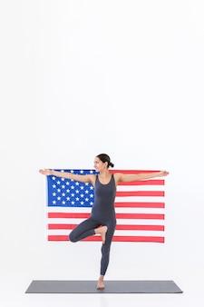 플래그와 함께 미국 여자 선수는 흰색 장면에 매트에 서있는 동안 요가 연습