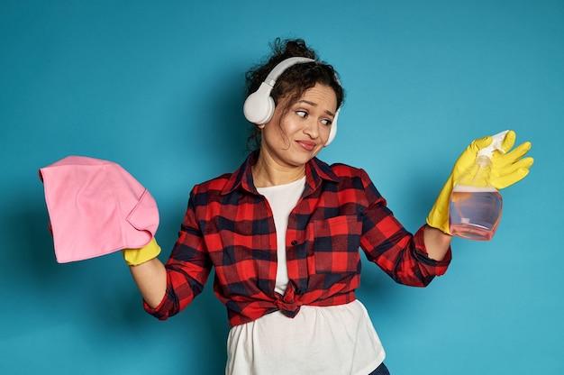 不快感を持ってスプレーを見て掃除雑巾を保持しているアメリカ人女性