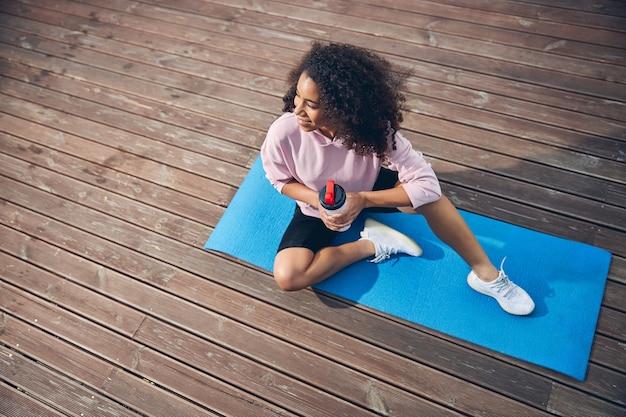 Американская женщина сидит на коврике для йоги и держит бутылку воды