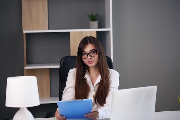 미국 여자 작업 노트북입니다. 사무실에서 랩톱 컴퓨터에서 작업 바쁜 비즈니스 여자.