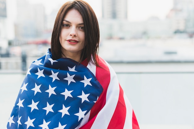 American woman wrapped in flag on independence day