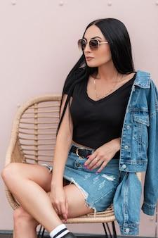 스커트에 블루 데님 재킷에 검은 탑에 선글라스에 미국의 젊은 힙 스터 여자는 분홍색 벽 근처 짚 의자에 앉아있다. 세련된 갈색 머리 소녀는 도시에서 휴식을 즐깁니다. 스트리트 스타일