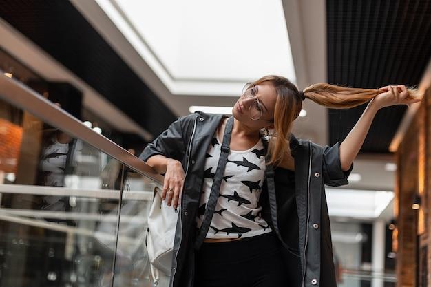 트렌디 한 헤어 스타일로 빈티지 안경에 세련된 옷을 입은 미국 젊은 여성이 서 있고 상점에서 머리카락을 유지합니다. 실내 아름 다운 여자 패션 모델입니다. 세련된 여성 의류.