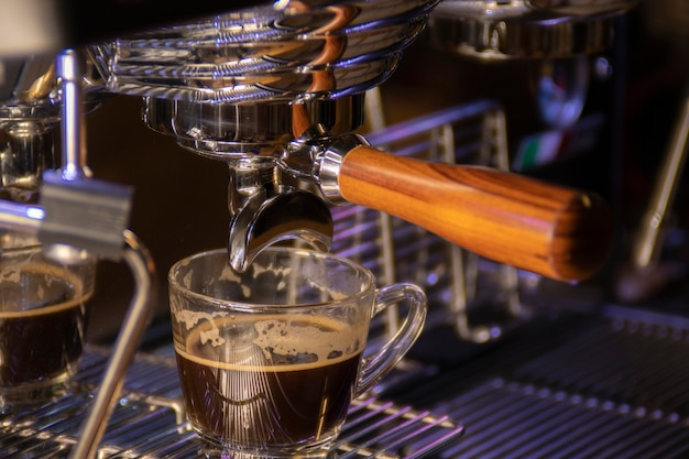 アメリカーノはコーヒーマシンから準備されており、コーヒーマシンはコーヒーをクローズアップしています。