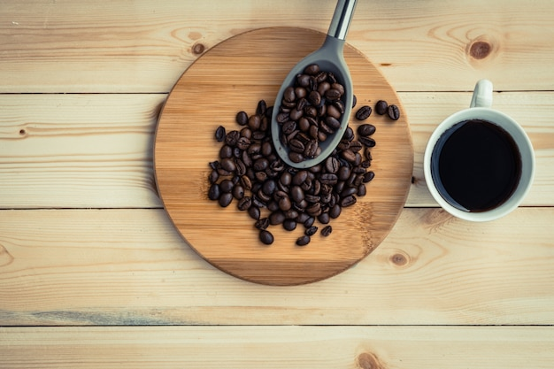 Americano coffee cup with roasted coffee bean in spoon place on the wooden table