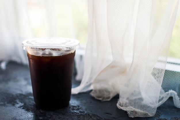 창문 근처에 있는 플라스틱 컵에 담긴 아메리카노 커피.
