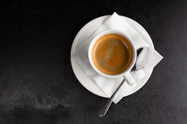 白いカップと黒の背景に受け皿のアメリカーノ